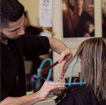 Homme coupant les cheveux d'une femme à l'aide d'un ciseau et d'un peigne